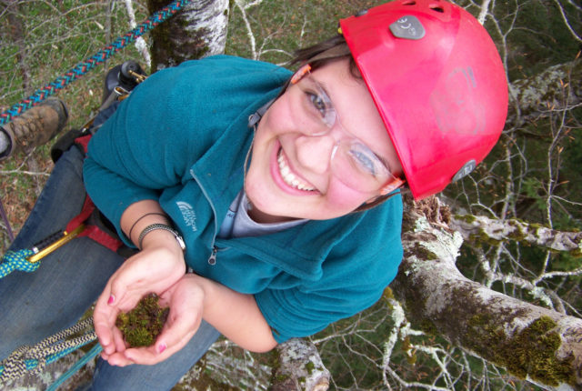 Student collecting moss from a tree