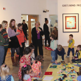 Students, parents and kids working on a quilt.