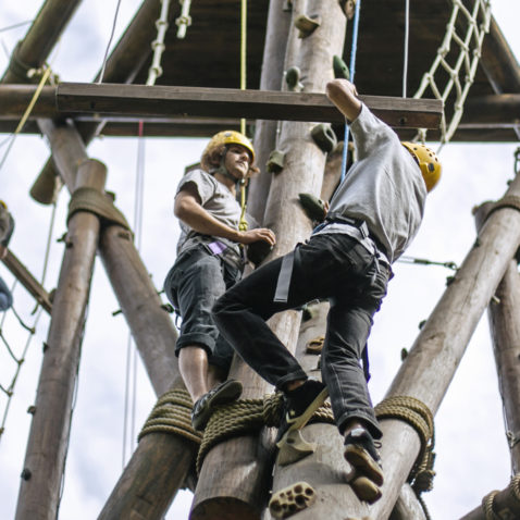 Students in harnesses climb a wooden structure